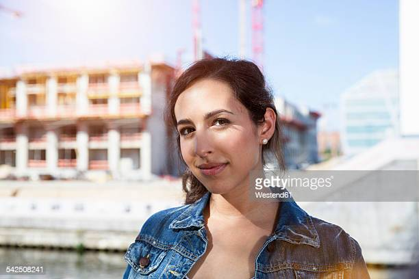 Germany, Berlin, portrait of smiling young woman in front of construction site