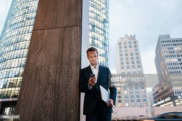 Germany, Berlin, Potsdamer Platz, businessman looking at his smartphone in the evening