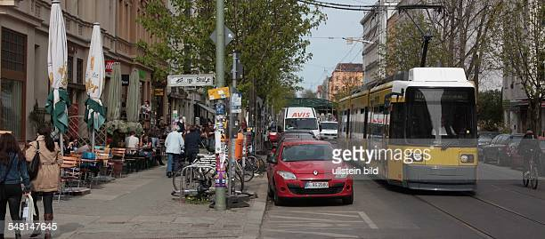 Germany Berlin Prenzlauer Berg - Kastanienallee, pavement cafe, parking cars at the roadside and tram