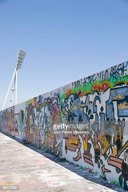 Germany, Berlin, Prenzlauer Berg, Mauerpark, Graffiti on wall with floodlight in background