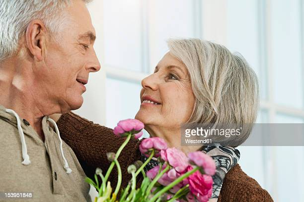 Germany, Berlin, Senior couple looking at each other, smiling