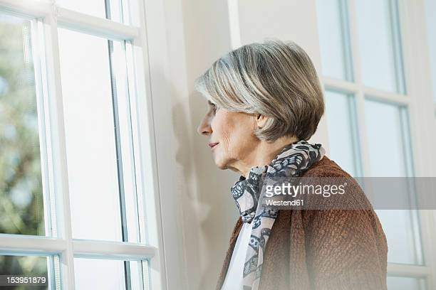 Germany, Berlin, Senior woman looking through window