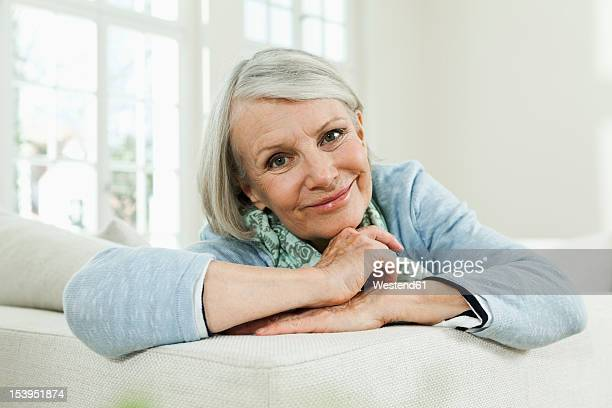 Germany, Berlin, Senior woman on couch, smiling, portrait