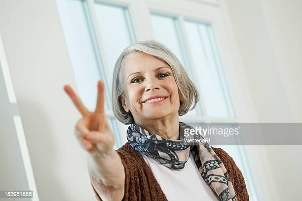 Germany, Berlin, Senior woman showing peace sign, smiling, portrait