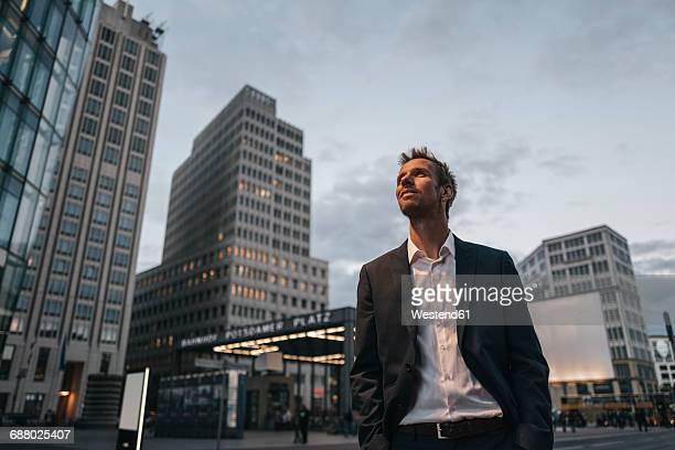 germany, berlin, smiling businessman at potsdamer platz in the evening - blick nach oben stock-fotos und bilder