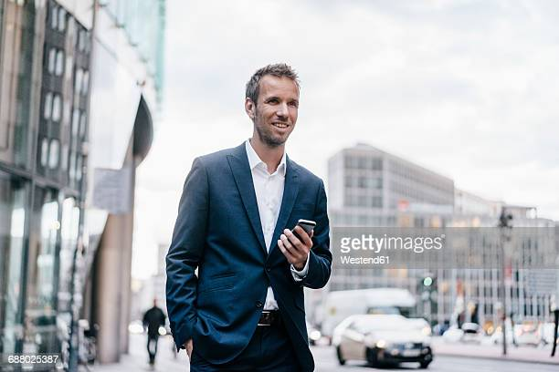 Germany, Berlin, smiling businessman with cell phone