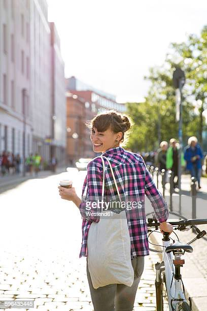 Germany, Berlin, smiling young woman with bicycle and coffee to go