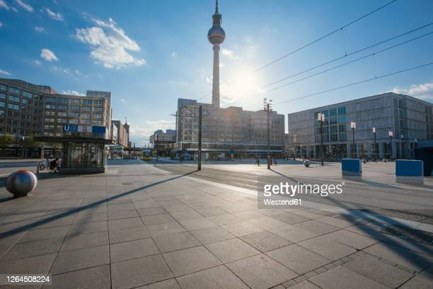 germany, berlin, sun shining over empty alexanderplatz during covid-19 pandemic - berlin stock-fotos und bilder