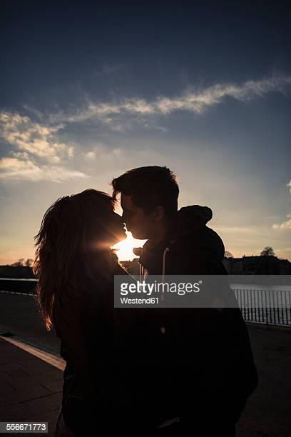 Germany, Berlin, teenage couple kissing on a promenade along a lake