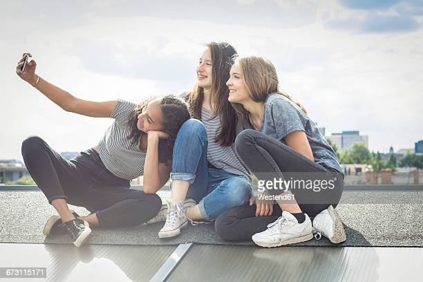Germany, Berlin, three friends sitting on roof top taking selfie with smartphone