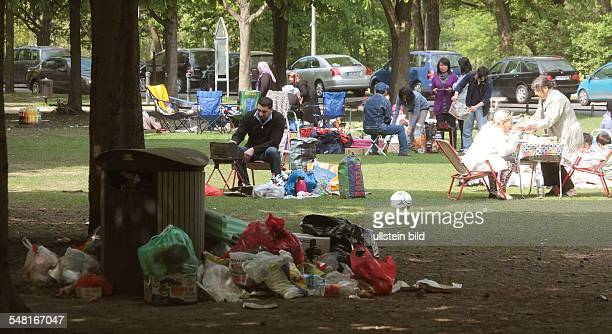 Germany Berlin Tiergarten overflowing garbage container after the Easter weekend in the Tiergarten park in the background families having a barbecue