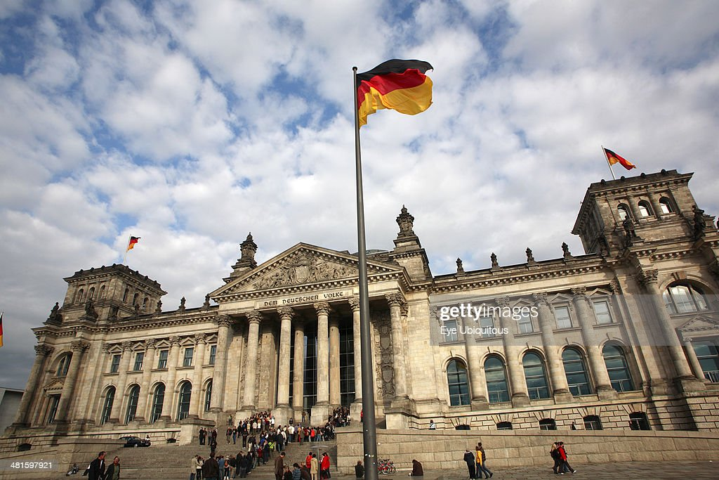 Tourist visitors outside entrance of the Reichstag building, German flag : News Photo