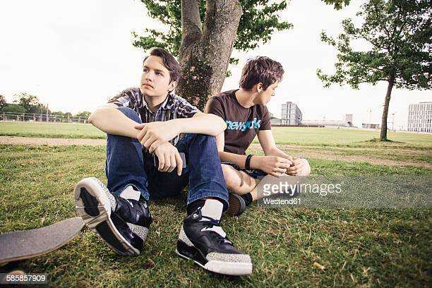 Germany, Berlin, two teenage boys in bad mood sitting under a tree
