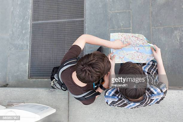 Germany, Berlin, two teenage boys looking at city map