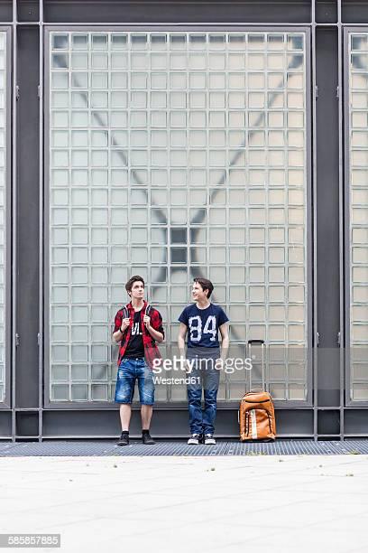 Germany, Berlin, two waiting teenage boys with baggage
