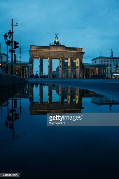 Germany, Berlin, view to Brandenburg Gate reflecting in puddle by night