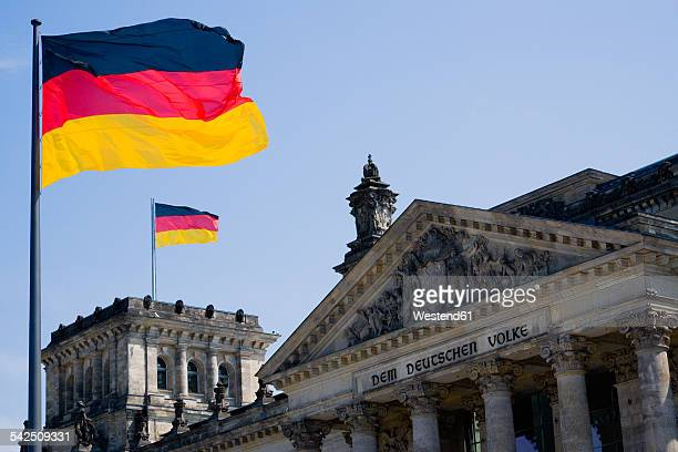 Germany, Berlin, view to upper part of Reichstag building with two German flags
