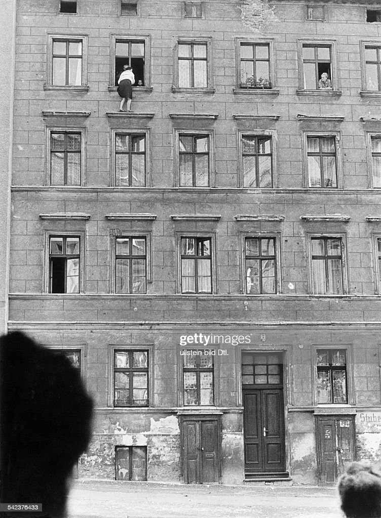 Germany, Berlin wallEscapes and escape attempts from East Germany Escape of a family of 3 persons from a building at 'Bernauer Street' that is situated right on the borderline between West and East Berlin; the woman standing on the ledge is waiting f : Foto jornalística