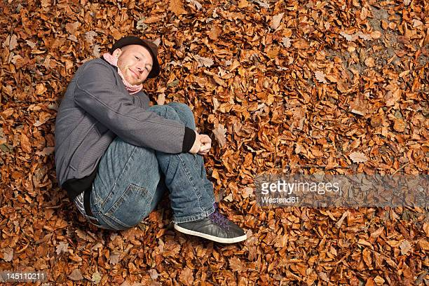 Germany, Berlin, Wandlitz, Young man lying in foliage, smiling, portrait