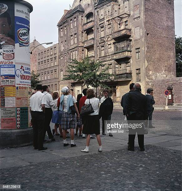 Germany Berlin Wedding Tourists viewing the bricked facades of houses at Bernauer Strasse 1966