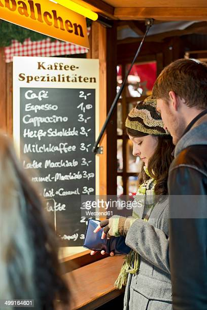 Germany, Berlin, young couple at Christmas market