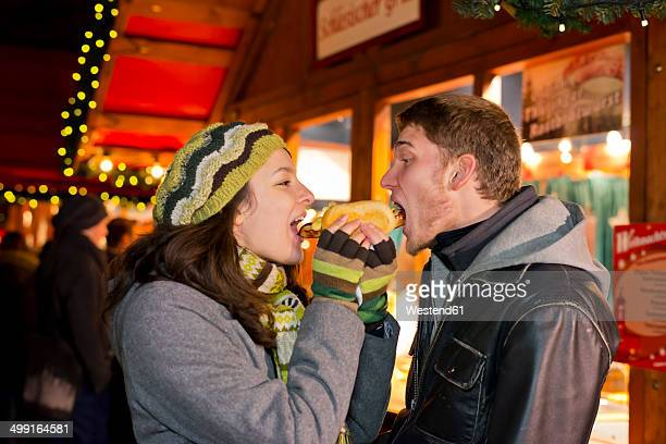 Germany, Berlin, young couple eating grill sausage at Christmas market