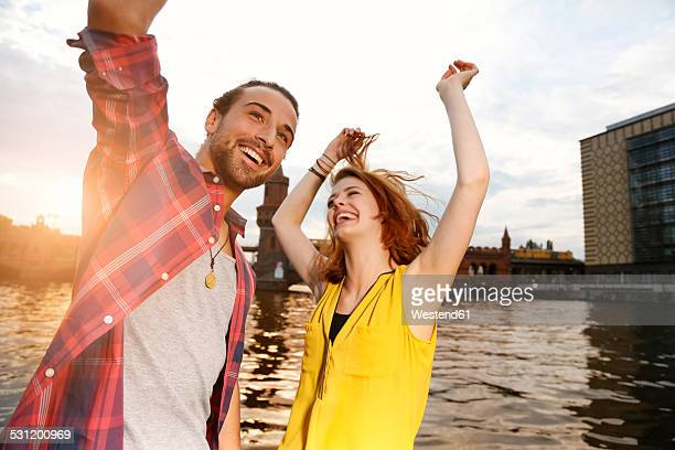 Germany, Berlin, Young couple enjoying sunset at Spree river