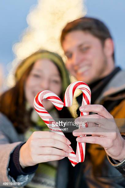 Germany, Berlin, young couple holding sugar canes formed as a heart