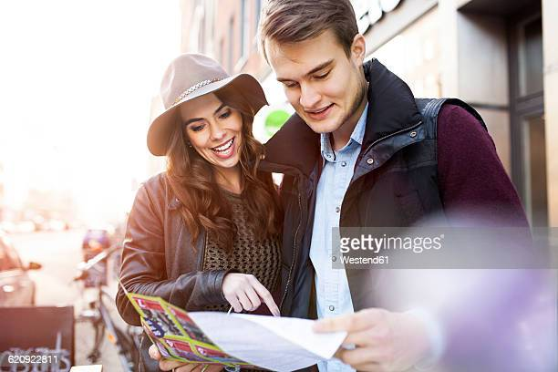 Germany, Berlin, young couple reading city map