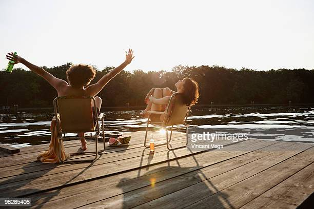 Germany, Berlin, Young couple relaxing on jetty, man holding beer bottle