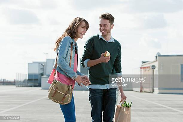 Germany, Berlin, Young couple standing on parking level laughing, man holding an apple, portrait