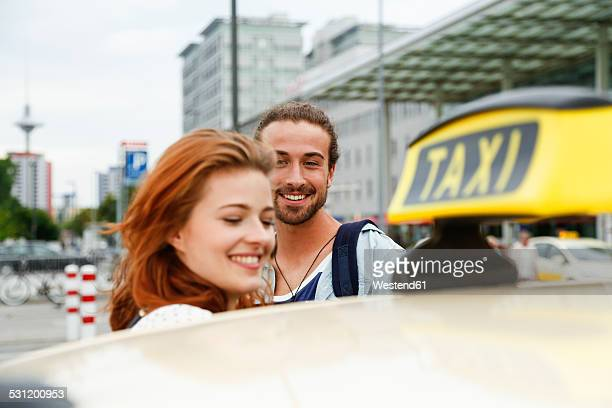 Germany, Berlin, Young couple taking taxi