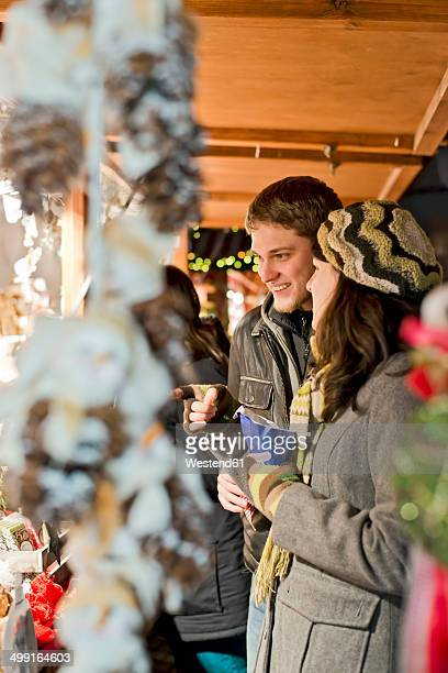 Germany, Berlin, young couple watching offerings at Christmas market
