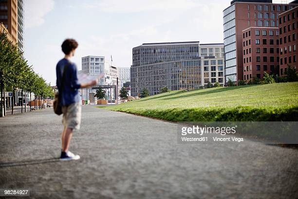 Germany, Berlin, Young man standing on street holding city map