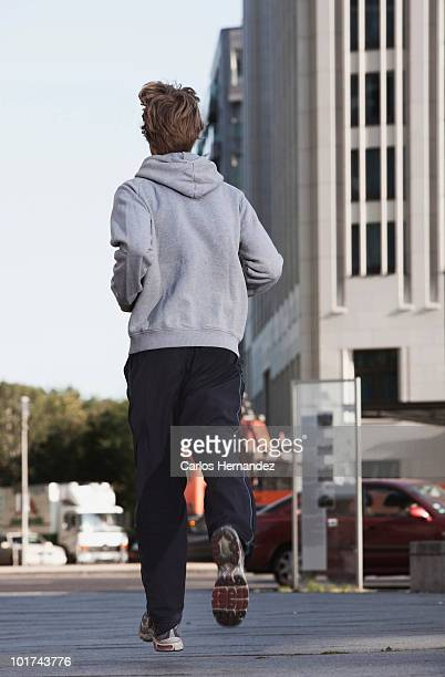 germany, berlin, young man jogging, skyscrapers in background - chándal fotografías e imágenes de stock