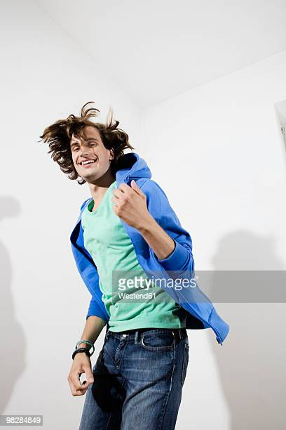 Germany, Berlin, Young man playing air guitar, smiling, portrait