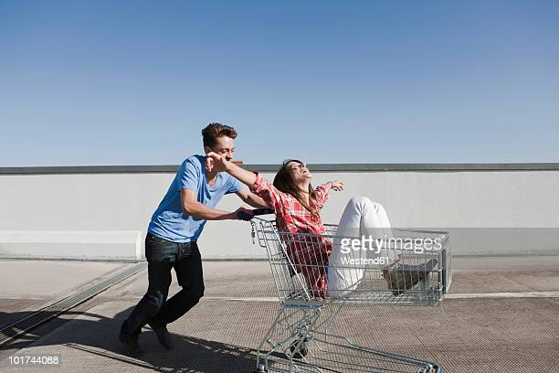 Germany, Berlin, Young man pushing young woman in shopping cart