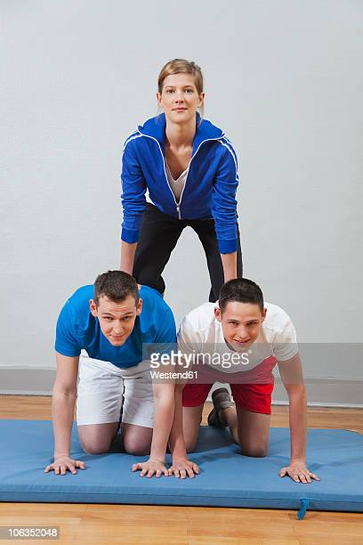 Germany, Berlin, Young men and women building human pyramid, portrait