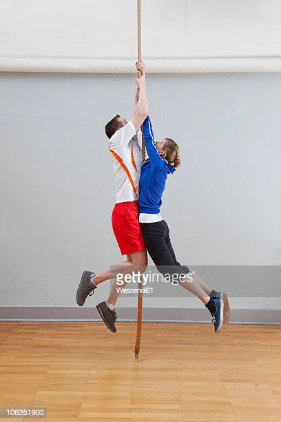 Germany, Berlin, Young men and women climbing rope in school gym