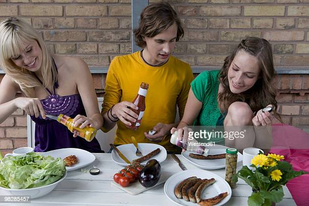 Germany, Berlin, Friends sitting at table having barbecue