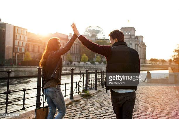 Germany, Berlin, young walking along River Spree high fiving