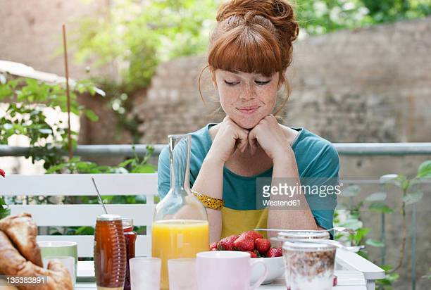 Germany, Berlin, Young woman at lunch table, smiling