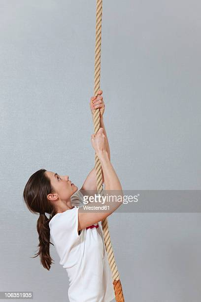 Germany, Berlin, Young woman climbing rope in school gym