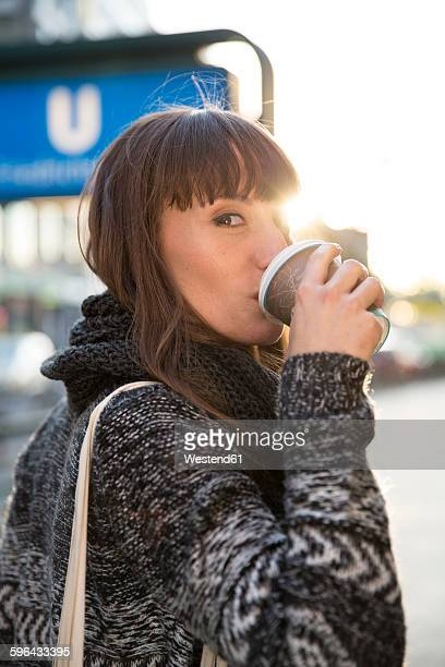 Germany, Berlin, young woman drinking coffee to go