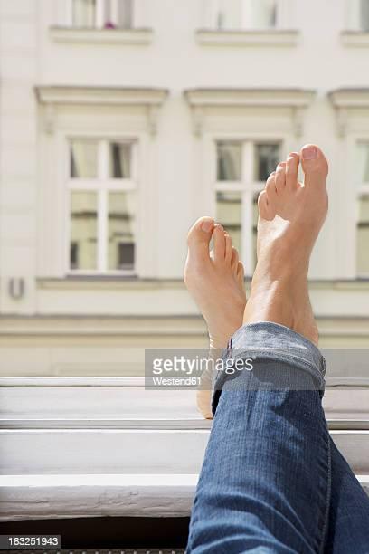 Germany, Berlin, Young woman feets on open window