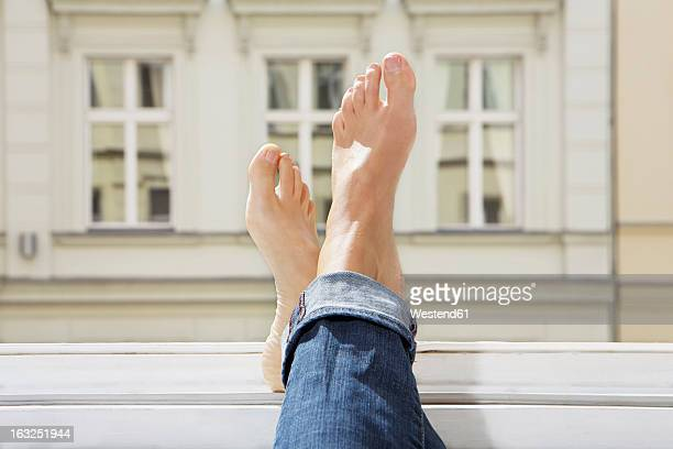 germany, berlin, young woman feets on open window - woman open legs stock photos and pictures