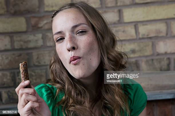 germany, berlin, young woman holding chocolate bar, portrait - essen mund benutzen stock-fotos und bilder