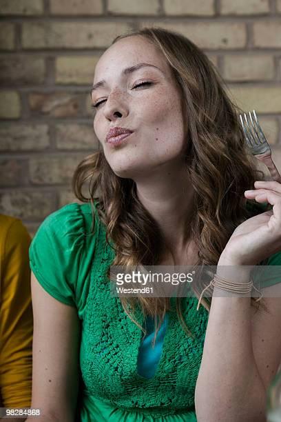 germany, berlin, young woman holding fork, eyes closed, portrait - üppig allgemein beschreibender begriff stock-fotos und bilder