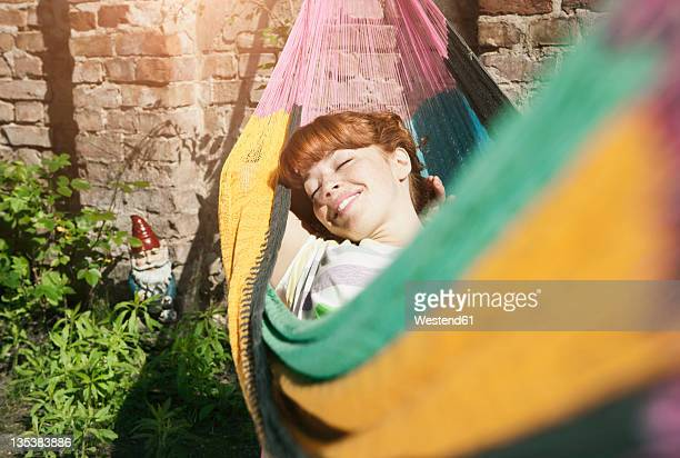 germany, berlin, young woman in hammock, smiling - entspannung stock-fotos und bilder