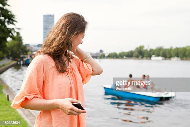 Germany, Berlin, Young woman listening music at Treptower Park